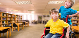 Composite image of happy boy pushing friend on wheelchair Royalty Free Stock Images
