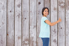 Composite image of happy brunette giving thumbs up Royalty Free Stock Image