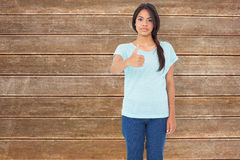 Composite image of happy brunette giving thumbs up Royalty Free Stock Photography