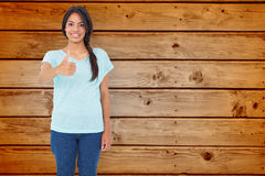 Composite image of happy brunette giving thumbs up Royalty Free Stock Images