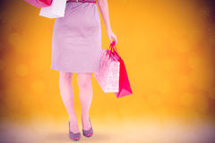 Composite image of happy brunette with shopping bags on the phone Stock Photo