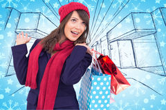 Composite image of happy brunette in winter clothes holding shopping bags Stock Image