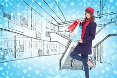 Composite image of happy brunette in winter clothes holding shopping bags Stock Photos