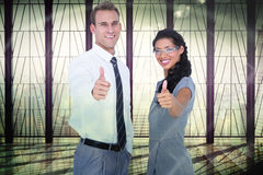 Composite image of happy business people looking at camera with thumbs up Stock Photo