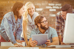 Composite image of happy business people using digital tablet at computer desk Royalty Free Stock Photo