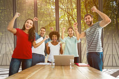 Composite image of happy business team with fists in the air. Happy business team with fists in the air against path in woods Stock Photo