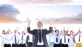 Composite image of happy businessman with arms raised Stock Image