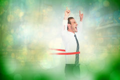 Composite image of happy businessman crossing the finish line and pointing up Stock Images