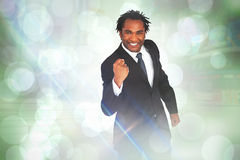 Composite image of happy businessman with fist Stock Photo
