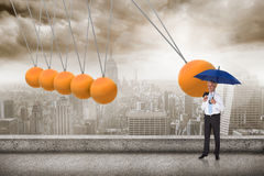Composite image of happy businessman holding umbrella Stock Photo