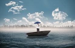Composite image of happy businessman holding umbrella in a sailboat Stock Images