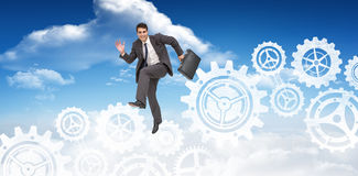 Composite image of happy businessman in a hurry Stock Photo