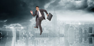 Composite image of happy businessman in a hurry Royalty Free Stock Photos