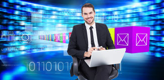 Composite image of happy businessman with laptop using smartphone Stock Photo
