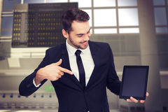 Composite image of happy businessman pointing with his tablet Stock Photos
