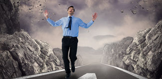 Composite image of happy businessman running with hands up Royalty Free Stock Photography