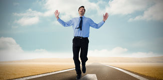 Composite image of happy businessman running with hands up Stock Photo