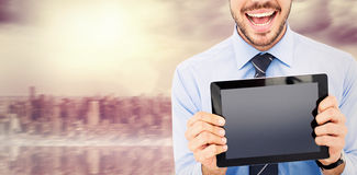 Composite image of happy businessman showing his tablet pc Royalty Free Stock Photography