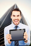 Composite image of happy businessman showing his tablet pc Stock Images