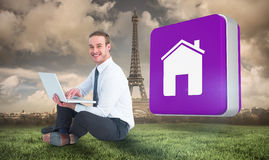 Composite image of happy businessman sitting and using laptop. Happy businessman sitting and using laptop against paris under cloudy sky Royalty Free Stock Image