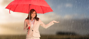 Composite image of happy businesswoman holding umbrella. Happy businesswoman holding umbrella against cloudy sky Royalty Free Stock Photography