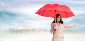 Composite image of happy businesswoman holding umbrella Royalty Free Stock Images