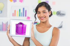 Composite image of happy businesswoman showing digital tablet in creative office Stock Image