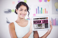 Composite image of happy businesswoman showing digital tablet in creative office Stock Photography