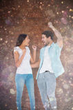 Composite image of happy casual couple cheering together Royalty Free Stock Images