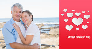 Composite image of happy casual couple embracing by the sea Royalty Free Stock Photography