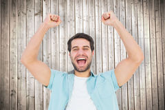 Composite image of happy casual man cheering at camera Stock Images