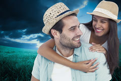 Composite image of happy casual man giving pretty girlfriend piggy back Royalty Free Stock Photos