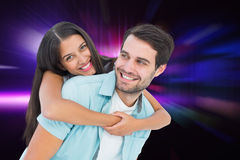 Composite image of happy casual man giving pretty girlfriend piggy back Stock Image