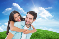 Composite image of happy casual man giving pretty girlfriend piggy back Stock Photos