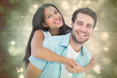 Composite image of happy casual man giving pretty girlfriend piggy back. Happy casual men giving pretty girlfriend piggy back against light design shimmering on Stock Photography
