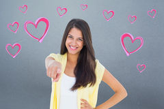 Composite image of happy casual woman pointing to camera Stock Photography