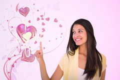 Composite image of happy casual woman pointing up. Happy casual woman pointing up against valentines heart design Royalty Free Stock Image