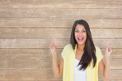 Composite image of happy casual woman pointing up Stock Images