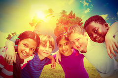 Composite image of happy children forming huddle at park Royalty Free Stock Images