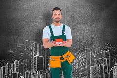 Composite image of happy construction worker holding house model Royalty Free Stock Image