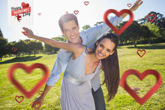 Composite image of happy couple with arms outstretched at park Royalty Free Stock Photography