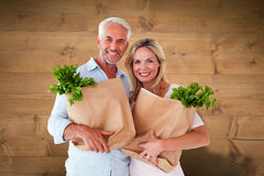 Composite image of happy couple carrying paper grocery bags Royalty Free Stock Image