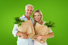 Composite image of happy couple carrying paper grocery bags Stock Photography