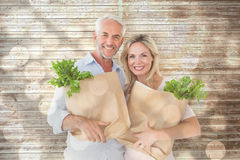 Composite image of happy couple carrying paper grocery bags Royalty Free Stock Photo