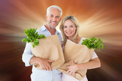Composite image of happy couple carrying paper grocery bags Stock Image