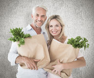 Composite image of happy couple carrying paper grocery bags Royalty Free Stock Photography