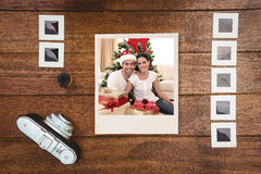 Composite image of happy couple celebrating christmas at home stock images