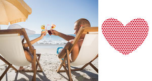 Composite image of happy couple clinking their glasses while relaxing on their deck chairs Stock Photos