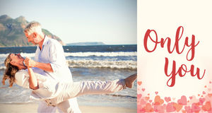 Composite image of happy couple dancing on the beach together Stock Images