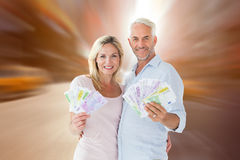 Composite image of happy couple flashing their cash Stock Image